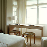 In this bedroom a monastic-looking reading bench-cum-desk has been placed in a deep window recess