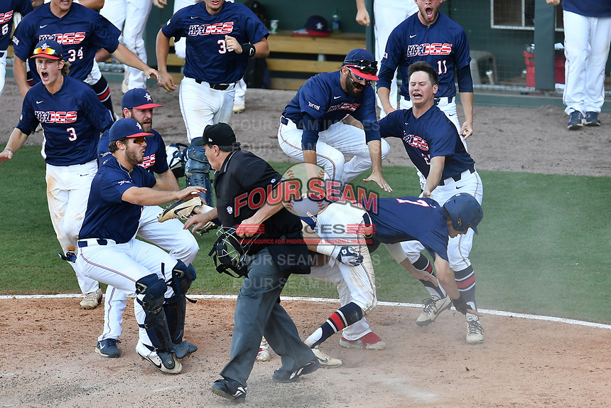 Home plate umpire Randy Vestal scurries to get out of the way as Branden Fryman (7) of the Samford Bulldogs scores the winning run in the bottom of the ninth inning as No. 6 seed Samford beat No. 1 seed Mercer, 5-4, at the Southern Conference Baseball Championship on Friday, May 26, 2017, at Fluor Field at the West End in Greenville, South Carolina. (Tom Priddy/Four Seam Images)