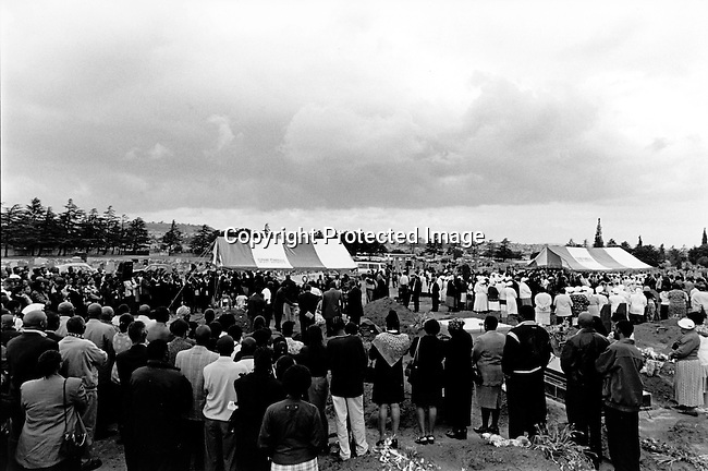 SOWETO, SOUTH AFRICA MAY 3: A funeral (far left) at Roodeport Cemetary for Jessica Ngcongwane, age 28, who died a few days earlier in an Aids related disease on May 3, 2003 in Soweto, South Africa. She was buried along with four other people on the same time. South Africa has seen a big increase in funerals since the HIV-Aids epidemic has grown and Jessica is one of many young people who are dying of HIV/Aids. Her family decided to come out in public about her disease to help other people get rid of the stigma about Aids in their communities. HIV-Aids affects many people in South Africa, but many still have problems to talk about it. South Africa has one of the highest aids infection rates in the world and its estimated that about six hundred people die each day..Photo: Per-Anders Pettersson/iAfrika Photos....