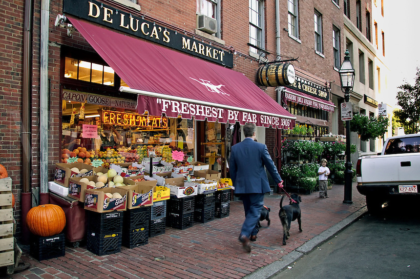 Man with dog walks past De Lucas Market and Deli on Charles Street on Beacon Hill Boston MA