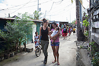 Myleene Klass, a high profile UK celebrity, violinist and pianist, walks through narrow urban slum alleyways with Irma Asoro (in pink), 29, who has been feeding her 4-month-old baby, Rashed James, formula since he was 2 days old, in Paranaque, Metro Manila, The Philippines on 19 January 2013. She thinks that formula is better for her baby even though the cost of formula and bottled water costs her more than double her rent, and she has to borrow from family and friends to pay for it. Photo by Suzanne Lee for Save the Children UK