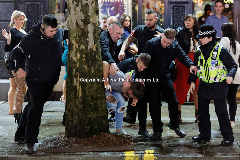 A police officer and club security personnel detain a man in Wind Street, Swansea, Wales  on Mad Friday, Booze Black Friday or Black Eye Friday, the last Friday night before Christmas Day, when traditionally people in the UK go out to celebrate the start of their holidays. Friday 22 December 2017