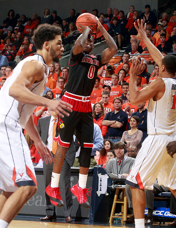 Louisville guard Terry Rozier (0) shoots between Virginia forward Anthony Gill (13) and Virginia guard Malcolm Brogdon (15) during the first half of an NCAA basketball game Saturday Feb. 7, 2015, in Charlottesville, Va. ( Photo/Andrew Shurtleff)