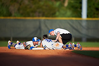 South Dakota State Jackrabbits second baseman Braeden Brown (32) gets checked by the athletic trainer as Gus Steiger (left) looks on during a game against the Northeastern Huskies on February 23, 2019 at North Charlotte Regional Park in Port Charlotte, Florida.  Northeastern defeated South Dakota State 12-9.  (Mike Janes/Four Seam Images)
