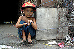 A boy in the Smokey Mountain neighborhood of Manila. The area is named for a now-closed garbage dump that dominates the area.