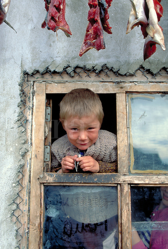 A 10 yr. old boy looks out of a window in his home; Salmon dry on a line above his head, Russian children, boys. Inuit child in Siberia. Inchoun Village Siberia Russia Village on the shores of the Arctic Ocean.
