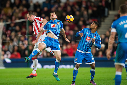 19.11.2016. Bet365 Stadium, Stoke, England. Premier League Football. Stoke City versus AFC Bournemouth. Stoke City midfielder Charlie Adam and Bournemouth midfielder Dan Gosling fight for the header as the ball travels towards Bournemouth midfielder Joshua King.