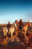 USA; Arizona; Monument Valley, Navajo Tribal Park, a Navajo man and his son ride on horseback with Mitchell Butte and Mitchell Mesa in the distance