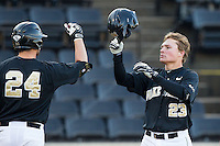Jimmy Redovian (23) of the Wake Forest Demon Deacons is greeted at home plate by teammate Charlie Morgan (24) after hitting a solo home run against the Georgetown Hoyas at Wake Forest Baseball Park on February 16, 2014 in Winston-Salem, North Carolina.  The Demon Deacons defeated the Hoyas 3-2.  (Brian Westerholt/Four Seam Images)