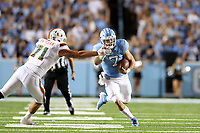 CHAPEL HILL, NC - SEPTEMBER 07: Sam Howell #7 of the University of North Carolina pushes past Scott Patchan #71 of the University of Miami during a game between University of Miami and University of North Carolina at Kenan Memorial Stadium on September 07, 2019 in Chapel Hill, North Carolina.