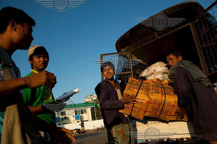 Dock workers unload a van in Yangon.