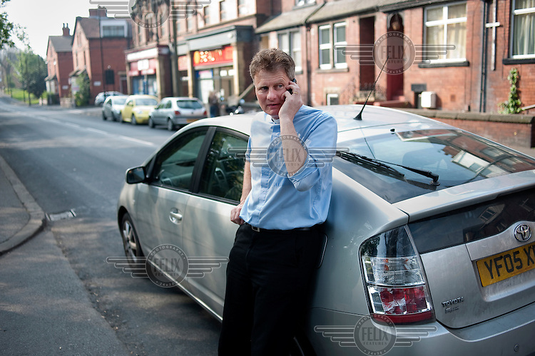 Priest Alistair Kaye, who helped Antonio try to win asylum, stands by his car whilst talking on his telephone in Leeds. Antonio's father committed suicide to stop him being deported back to Angola.