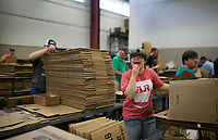 NWA Democrat-Gazette/Charlie Kaijo Amber Hamblin of Pea Ridge laughs while inspecting used Walmart boxes to be reused or recycled on Monday, October 9, 2017 at Open Avenues in Rogers. Many of clients develop close relationships with one another. The organization partners with 22 different businesses and provides job and life skills training to people with disabilities, currently serving 110 clients. The clients work on projects at work stations and are paid for their work. This year they have focused on transitioning their clients into jobs in the community, many with Walmart, Zaxbys and Harp's.