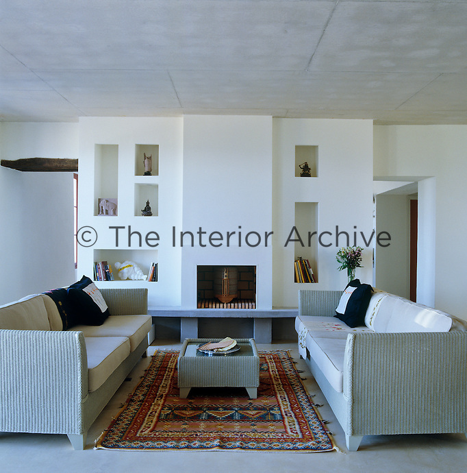Niches filled with objects and small sculptures surround the fireplace and a pair of Lloyd Loom sofas flanks a matching coffee table in this cool and simple living room