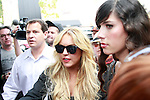 US actress Lindsay Lohan (center) with her bodyguard (left) in Los Angeles, California 09 May 2008. The actress is doing a photo shoot for her new leggings line on Robertson Boulevard and wanted the paparazzi to join her.