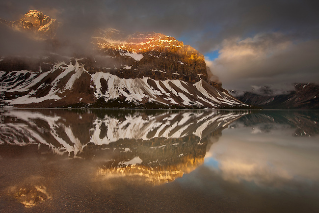 The mountains are lit up over the glass-like water of Bow Lake at sunrise after a stormy night in June 2012, Banff National Park, Alberta, Canada.  Photo by Gus Curtis.