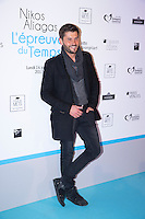 French TV host Christophe Beaugrand poses during a photo call for the opening of a photography exhibition by French-Greek TV host Nikos Aliagas, on January 16, 2017, in Paris.