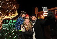NWA Democrat-Gazette/ANDY SHUPE<br /> Bennjamin Banks (right) takes a selfie with his wife, Kristianne and sons Bear (left), 10, and Super Tristan, 8, Saturday, Nov. 21, 2015, after the lighting ceremony for the Winter Wonderland holiday lights display on the Bentonville square. The display has been expanded this year to include more lights and more color.