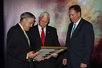 In this photo released by the National Aeronautics and Space Administration (NASA) United States Vice President Mike Pence receives a commemorative montage including an Indiana flag, representing the Vice President's hometown, that was flown in space, from NASA's Kennedy Space Center (KSC) Director, Robert Cabana, left, and Acting NASA Administrator, Robert Lightfoot, right, Thursday, July 6, 2017, in the green room at NASAís Kennedy Space Center (KSC) in Cape Canaveral, Florida. Vice President Mike Pence is scheduled to speak at the event to highlight innovations made in America and tour some of the public/private partnership work that is helping to transform the center into a multi-user spaceport. Photo Credit: Aubrey Gemignani/NASA/CNP/AdMedia