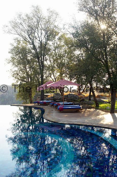 Sun loungers beside the swimming pool at the Singita Pamushana Lodge, Malilongwe Trust, Zimbabwe