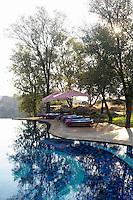 Sun loungers beside the swimming pool at the Singita Pamushana Lodge, Malilongwe Trust, Zimbabwe