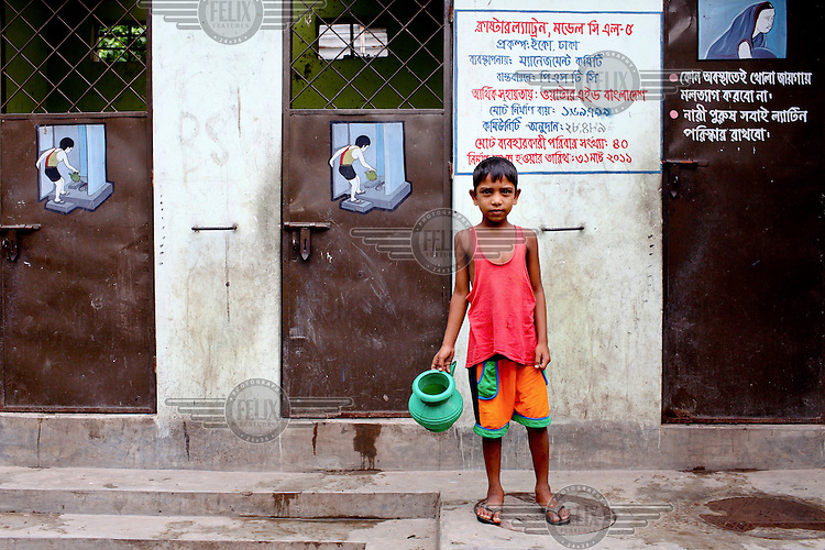 A child comes out from a public toilet in the TT Para Slum.