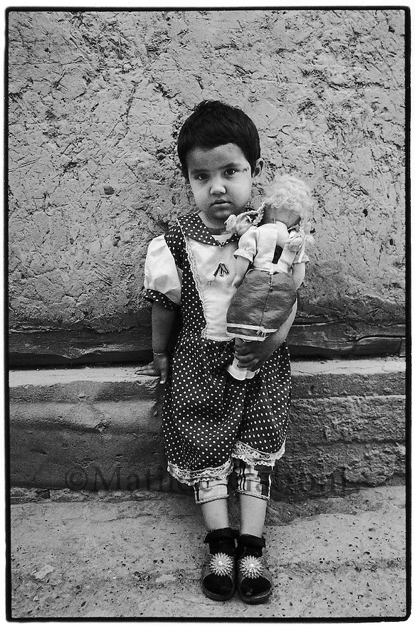 Uzbekistan - Bukhara - Little girl holding her doll standing in the street.