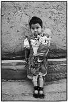 Uzbekistan - Bukhara - Little girl holding her doll standing in the street.
