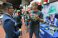 Erik Salgvero (left), a senior mechanical engineer student at the University of Arkansas, speaks with Brian Henry, a lean six sigma black belt with Schlumberger, Wednesday, March 11, 2020, during the Science, Technology, Engineering and Math (STEM) Career Fair inside Bud Walton Arena in Fayetteville. The STEM Career Fair, hosted by the University Career Development Center and the College of Engineering, allowed students to identify employment opportunities, expand their network, polish their interview skills, learn industry information and gather information about companies. Check out nwaonline.com/200312Daily/ and nwadg.com/photos for a photo gallery.<br /> (NWA Democrat-Gazette/David Gottschalk)