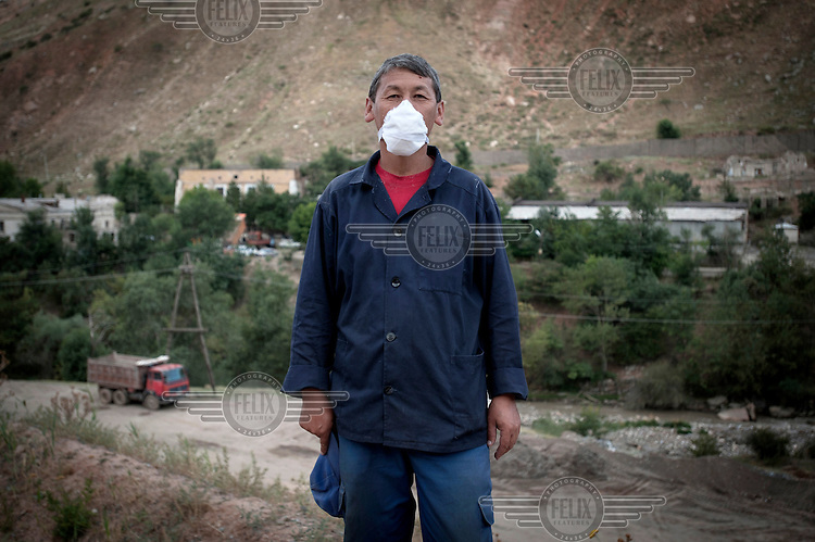 Iman Murzabekh, 43, stands at the entrance of the Dump No.3 where he works checking trucks that travel between Dump No.3 and Dump No.6. Workers make about 20,000 Somoni (GBP 2,650) in 2 weeks. Due to the pollution they ingest while working, staff work two weeks on and two weeks off....