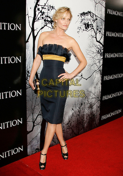 "AMBER VALLETA.""Premonition"" World Premiere held at the ArcLight Cinerama Dome Theatre, Hollywood, California, USA..March 12th, 2007.full length black dress yellow band belt hand on hip strapless clutch purse .CAP/ADM/RE.©Russ Elliot/AdMedia/Capital Pictures"