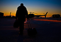 Aircraft pilot Charles Paquin walks with his suitcase in front of an helicopter at the Quebec City Jean Lesage International Airport, also known as Jean Lesage International Airport (French: Aeroport international Jean-Lesage de Quebec, or Aeroport de Quebec) (IATA: YQB, ICAO: CYQB) November 11, 2009.