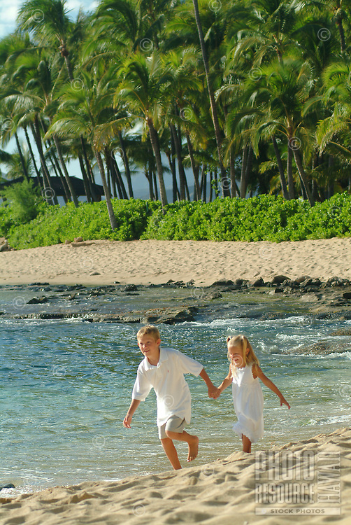Young brother and sister holding hands and running on the beach on West Oahu