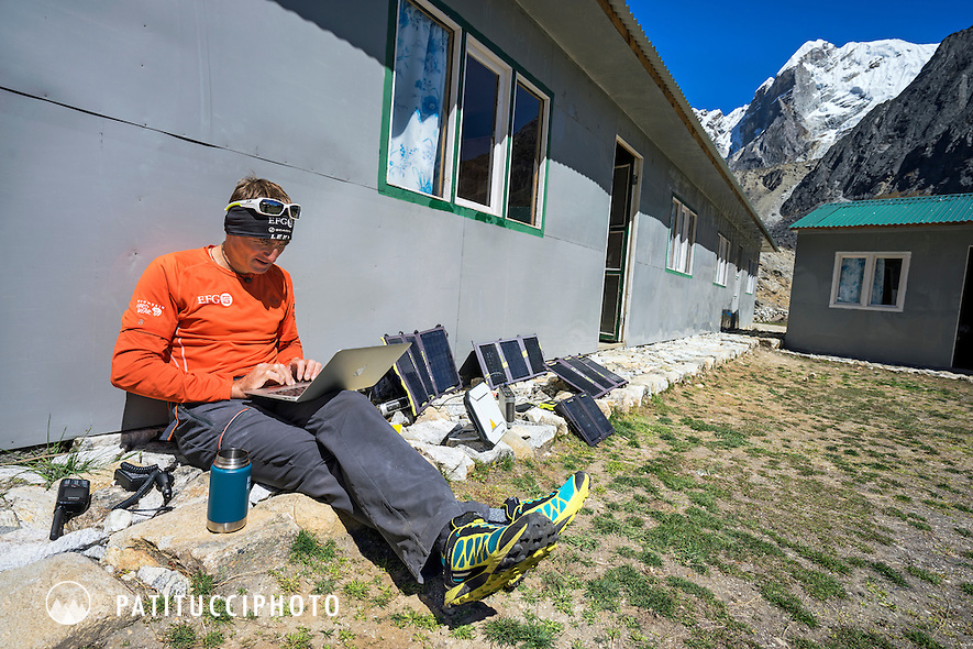 Ueli Steck in the Cholatse basecamp guesthouse in Dzongla, using a laptop computer, internet base station and solar panels to get online while on a climbing expedition in Nepal.