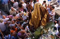 Assumption Day procession of people carrying a statue of the Virgin Mary through the streets of Panier, Marseille, France.