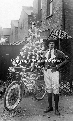 "Decorated bicycle and man in fancy dress. Some sort of celebration or fete in Barking east London. A real photo postcard probably only one copy printed. Never sent. Probably circa 1910 1920. The photographs is taken by ""Glass and Son. ZH7 Barking East."""
