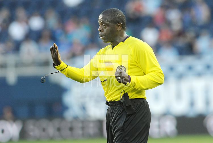Referee Abiodun Okilaja gives out a yellow card... Sporting KC defeated FC Dallas 2-1 at LIVESTRONG Sporting Park, Kansas City, Kansas.