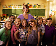 A female teacher gather's her students around inside of their classroom.