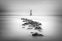 A long exposure photograph of small rocks leading towards a distant lighthouse during high tide.