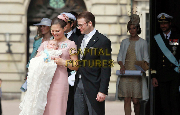 Baptism Estelle Silvia of Sweden Ewa Mary, Duchess of ?sterg?tland, born on 23 February at 4.26 clock, daughter of Crown Princess Victoria of Sweden, her husband Prince Daniel Duke of V?sterg?tland (Westling), before the Castle Church in Stockholm, Sweden, 22nd May 2012.royals royalty pink dress baby kid child family black suit glasses white blanket half length looking down profile .CAP/PPG/WS.©Willi Schneider/People Picture/Capital Pictures