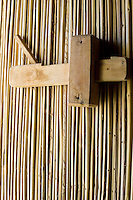 A door made from the ribs of palm fronds has a simple but effective wooden latch