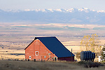 old red barn and partial farmhouse with views of the tobacco root mountains in montana