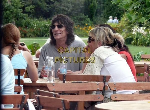RONNIE WOOD & FRIENDS.Enjoying a day out at RHS Wisley Gardens near Guildford, Surrey, England..July 26th, 2008.half length grey gray top sunglasses shades table bottled water.CAP/BC.©BC/Capital Pictures.
