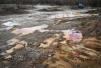 Puddles below the artificial dam in Mitrovica after the rain. The dam is built from tailings, the remnants from processing of lead and zinc ores, and altough the crest of the dam is now rehabilitated, the water is still colored red because of heavy metals.
