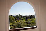 Arched decorated Moorish stone window looking over gardens, Generalife garden, Alhambra, Granada, Spain