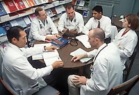 A group of Medical Residents sitting at a table discussing healthcare.