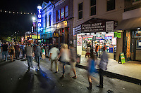 Patrons walk up and down 6th Street, Austin's famous bar district with hundreds of bars and live music venues. 6th Street has been a major entertainment district since the 1970s. Many bars, clubs, music venues, and shopping destinations are located on East 6th Street between Congress Avenue and Interstate 35, and many offer live music at one time or another during the week. Traffic is generally blocked on East 6th Street and most crossroads from I-35 to Brazos Street on weekend evenings, and football home games (depending on pedestrian traffic), as well as holidays and special events, to allow the crowds to walk unfettered to the many venues that line the street.
