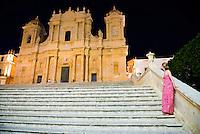 Noto at night, woman at Noto Cathedral (St Nicholas Cathedral, Cattedrale di Noto), Sicily, Italy, Europe. This is a photo of a woman at Noto Cathedral (aka St Nicholas Cathedral, Cattedrale di Noto) in Noto at night.