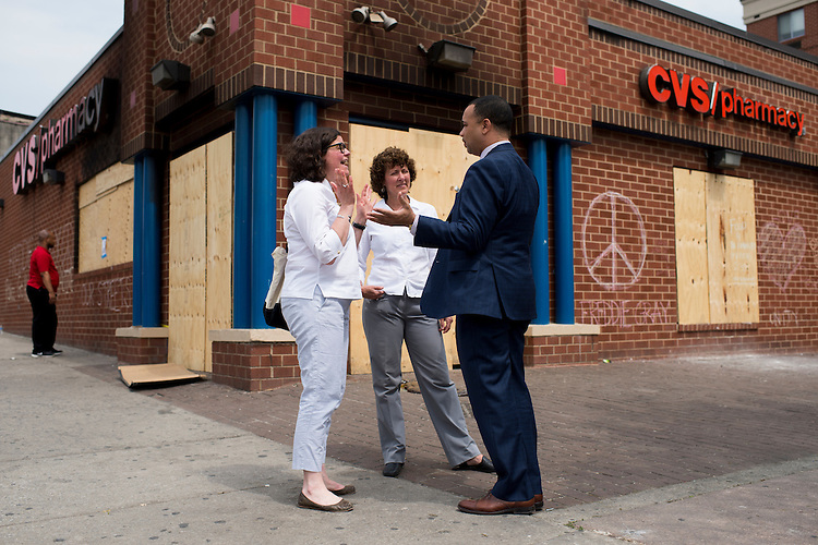 UNITED STATES - MAY 5: From left, Democratic campaign consultant Martha McKenna, Maryland House Del. Shelley Hettleman, and Maryland Del. Antonio Hayes, talk outside of the burned out and looted CVS, next to the Penn North Plaza senior living facility, in Baltimore on Tuesday, May 5, 2015. In the wake of the unrest in Baltimore, McKenna organized food deliveries, and on this day, flower deliveries to senior citizen facilities in the areas of the city affected by the Freddie Gray riots. (Photo By Bill Clark/CQ Roll Call)