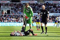 Pictured: Newcastle goalkeeper Tim Krul helps team mate Mathieu Debuchy with his leg cramp. Saturday 19 April 2014<br />